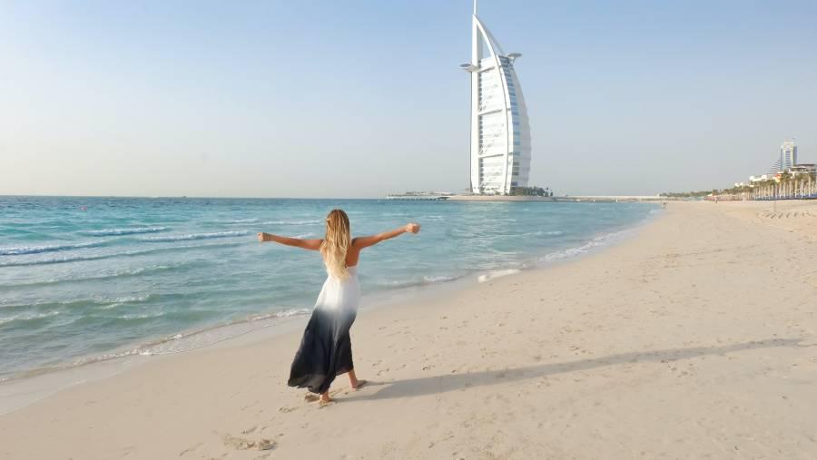Burj Al Arab in Dubai and a Girl on the beach in front of the 7 star hotel Burj Al Arab in Dubai